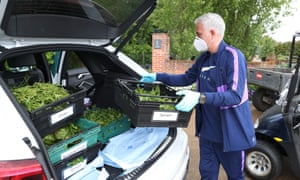 Tottenham's manager, José Mourinho, helps to move food being given to families in need.