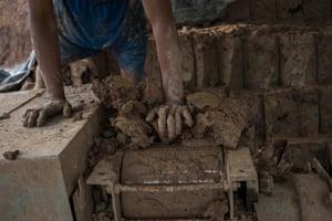 Boran feeds clay into a brick-moulding machine