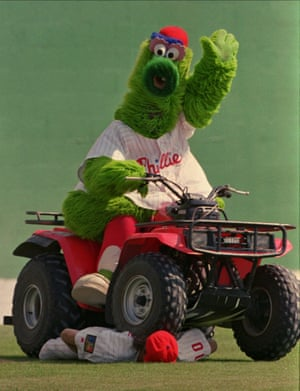 The Phillie Phanatic on his quad bike rides over a dummy dressed in a Phillies uniform and identified as Darren Daulton during the filming of a promotional advert in 1996.
