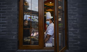 A Chinese cooks wears a protective mask as he works in a restaurant on a commercial street on 2 June, 2020 in Beijing, China.