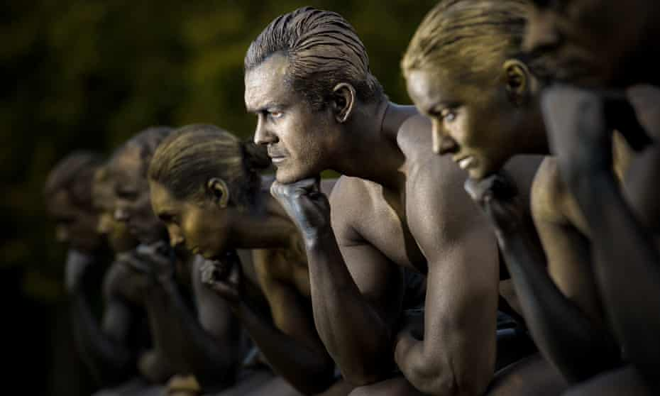 Nine models posed as Rodin's The Thinker mark the launch of the Nine Dots prize