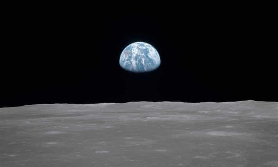 Earth rising over the moon's horizon.