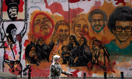 A  woman speaks on a mobile phone while walking past murals of people killed during Egypt's uprising near Tahrir Square in Cairo