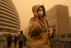 Beijing, China: A woman shields herself from heavy winds while commuting during a sandstorm.