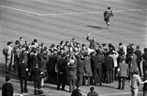 The England captain, Bobby Moore, holds the Jules Rimet trophy aloft surrounded by press and photographers