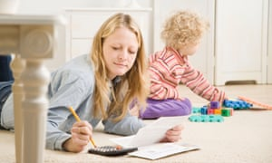 Mother working on calculator while child plays
