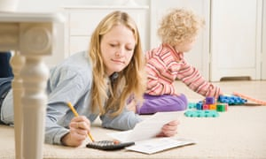 A woman works from home as her toddler plays nearby