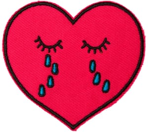 Sew-on patch in shape of red heart with blue tears falling from closed eyes. '