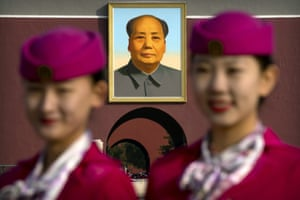 Hospitality staff members pose for a group photo near the large portrait of Mao