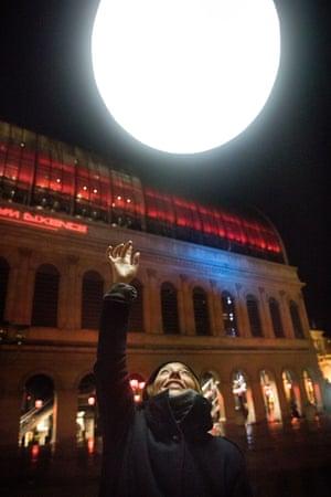 A woman reaches up towards a ball of light, part of La Pêche aux Gouttes, by Plasticiens Volants, on Place Louis Pradel