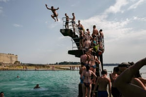 People queue to dive into the landmark sea pool of Saint-Malo in Brittany as a new heatwave blasted into northern Europe that set records in several countries.