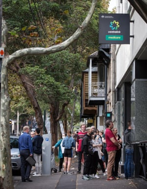 People queue along Crown Street in Sydney's Darlinghurst on Monday to get into the Centrelink offices.