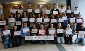 Scientists hold placards saying where they are from