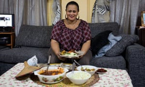 Senait Neftalem sitting on a sofa, holding a plate of food with several dishes on the table in front of her