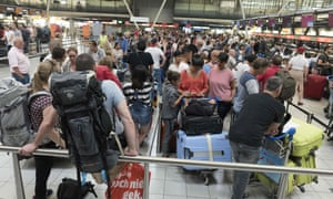 Passengers queue to check in at Schiphol airport in July.