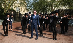 Protesters dressed in top hats and a mask of Britain's Prime Minister David Cameron protest against British owned-tax havens during the Global Anti-corruption Summit in London