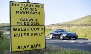 A car drives passed a sign which says 'Welsh COVID rules apply stay safe'