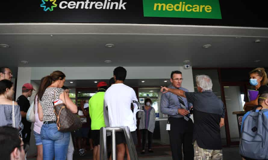 People queue outside the Centrelink office in Southport on the Gold Coast