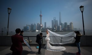 <strong>Shanghai, China</strong><br>A woman poses for wedding pictures at the Bund in front of the financial district of Pudong