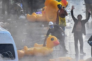 Protesters stand with oversized inflatable rubber ducks in front of police water cannon trucks during an anti-government rally in Bangkok on November 17