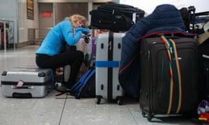 A traveller sleeps next to luggage at Heathrow