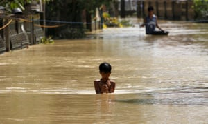 A boy wades through a flooded street in Jaen, Nueva Ecija, in northern Philippines: the death toll from Typhoon Koppu has now risen to 54.