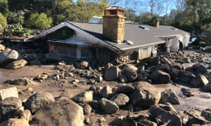 In this photo provided by Santa Barbara County fire department, Kerry Mann navigates the large boulders and mudflow that destroyed the home of her friend in Montecito, California.