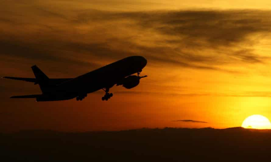 A plane takes off as the sun rises