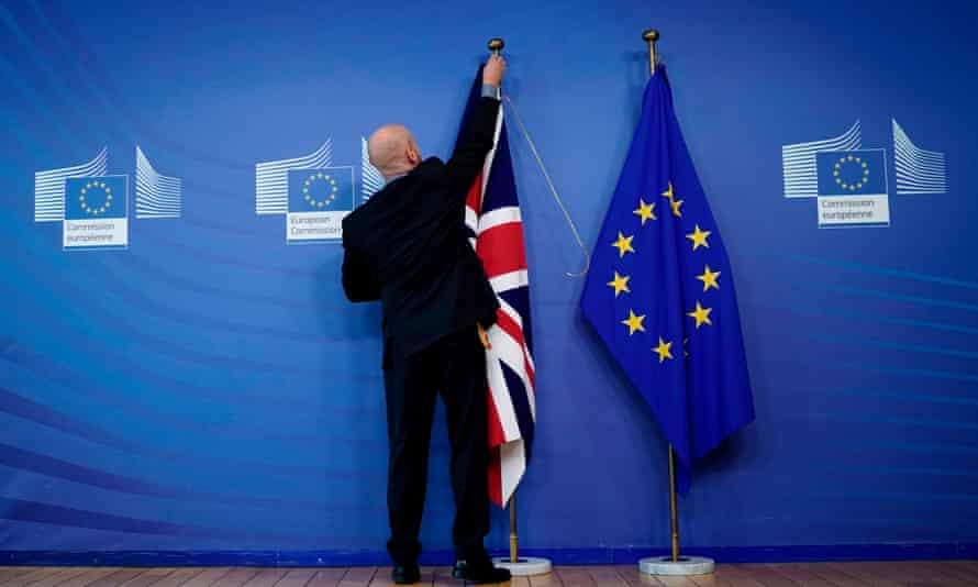 An official hangs a union flag next to an EU flag at the European Union headquarters in Brussels