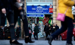 People walk past a sign for the Scotsman newspaper in Edinburgh, Scotland