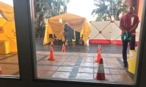 A medical tent erected outside the hotel, with a man who appears to be a doctor wearing a protective suit.