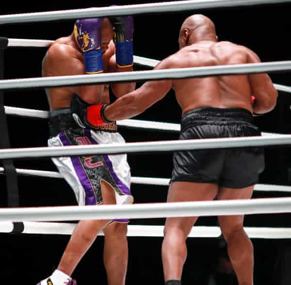 Mike Tyson (right) gets a body shot in.