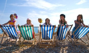 Kids sitting on striped sunloungers at the beach