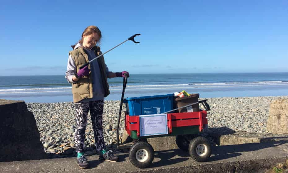 Skye Neville at the beach with a trolley and a litter-picking tool