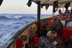 A migrant reads verses of the Quran aboard the Open Arms Spanish humanitarian boat as it nears Lampedusa in southern Italy