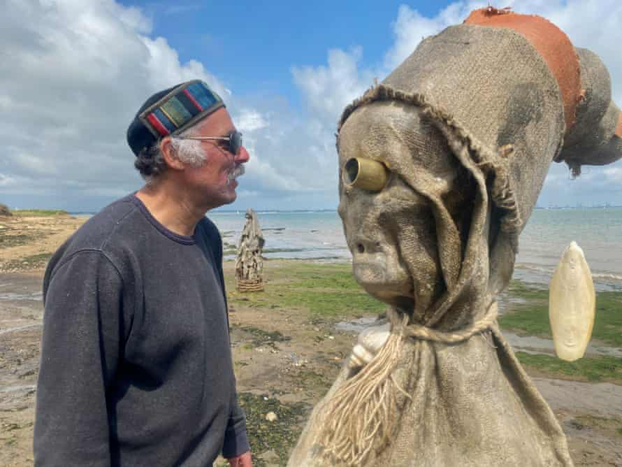 Artist Nabil Ali with a figure from his Essex beach installation, The Sea People