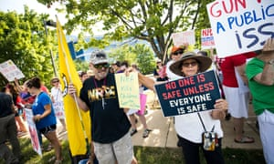 National Rifle Association supporters stand among gun control advocates as they rally outside the NRA headquarters in Fairfax, Virginia.