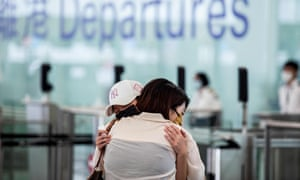 Friends embrace at the departure gates before a flight to London from Hong Kong airport