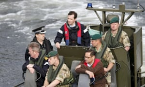 George Osborne (rear left) arrives by boat at the jetty at the Royal Navy's submarine base at Faslane.