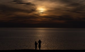 People watch the partial solar eclipse through the clouds at sunrise from the shoreline in Winthrop, Massachusetts, US