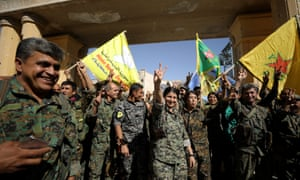 Syrian Democratic Forces fighters make victory signs in Raqqa.