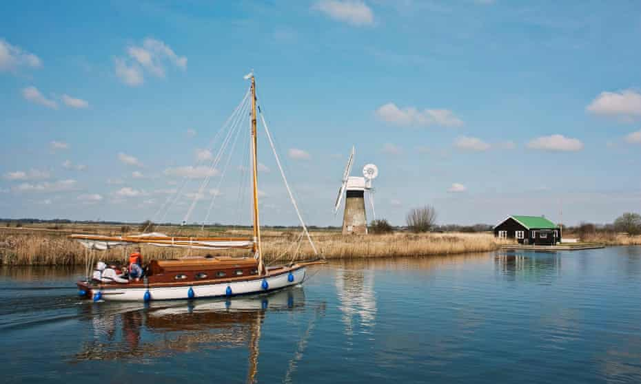 A sail boat meanders along the Norfolk Broads at Thurne