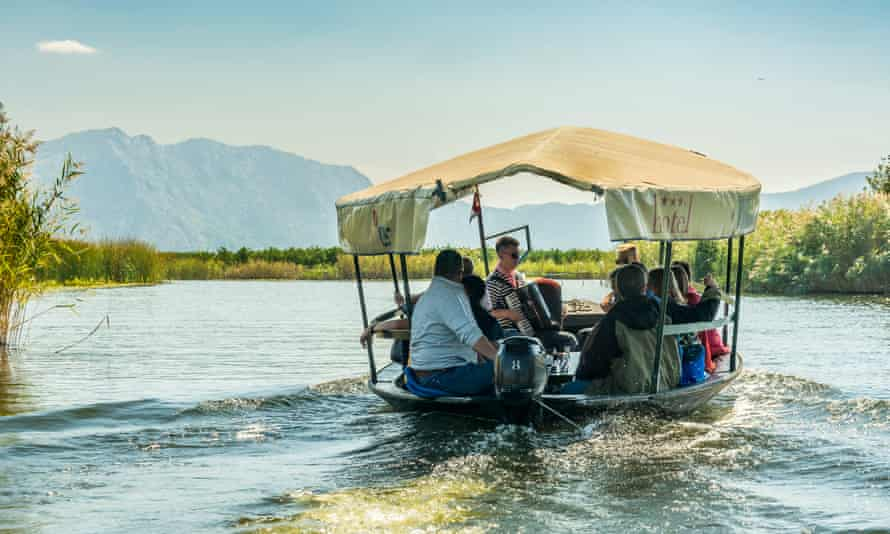 Visitors take a boat trip in the Neretva river delta and are entertained by tradtional musicians.