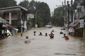 Residents negotiate a road flooded due to Typhoon Vamco.
