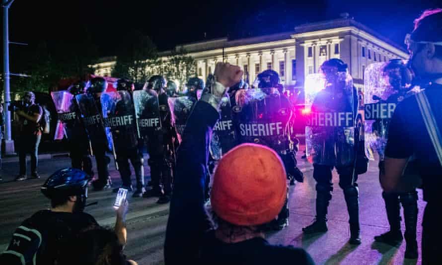 Demonstrators sit in the street, in front of law enforcement in Kenosha, Wisconsin.