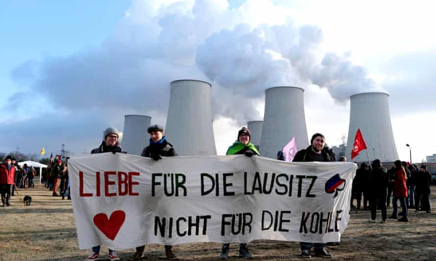 Climate activists in front of the coal-fired Jaenschwalde power station in the Lausitz region, Germany, protesting against open-cast mining in November 2019. Their banner reads: 'Love for the Lausitz. Not for the coal.'