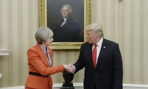 May and Trump hold hands in front of a portrait