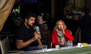 A woman smokes in an Athens bar. Few measures have been as controversial as official efforts to wean Greeks off nicotine.