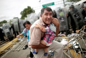 A Honduran migrant protects his child after fellow migrants, part of a caravan trying to reach the U.S., stormed a border checkpoint in Guatemala, in Ciudad Hidalgo, Mexico October 19, 2018