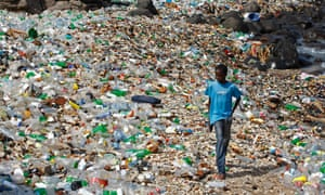 A boy walks along a polluted beach strewn with predominantly plastic bottles in the village of Ngor, Dakar, Senegal